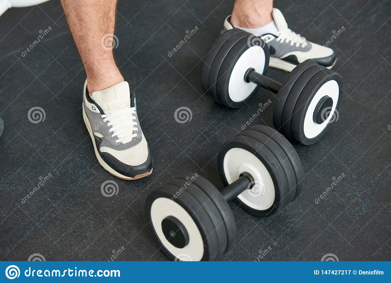Sportsman in sneakers standing with dumbbells on the floor.