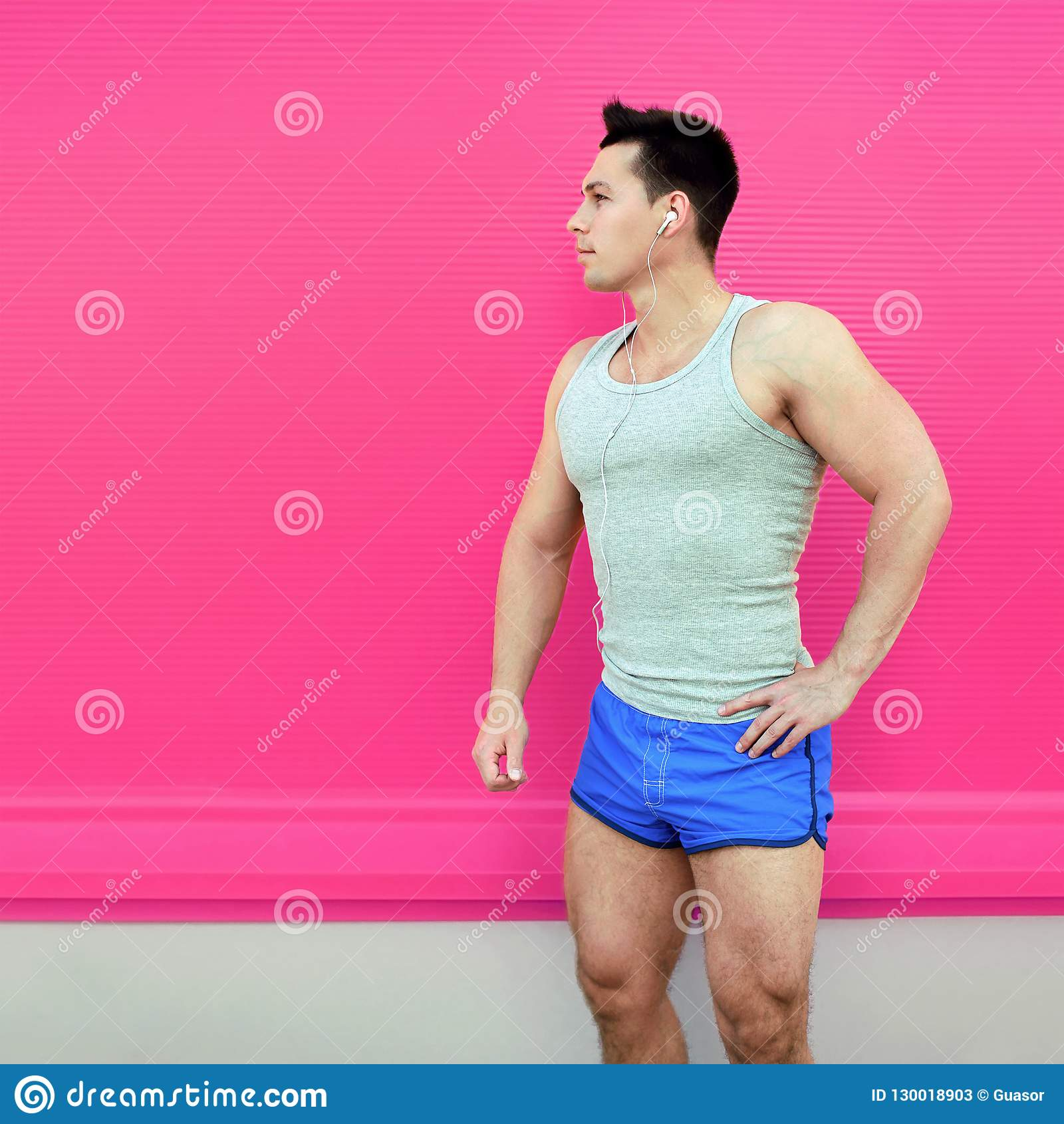 Sportsman stands in shorts on colorful pink wall background