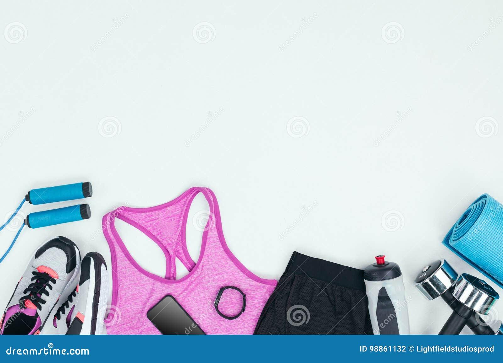Sportswear com sapatilhas, smartphone, perseguidor da aptidão e equipamento da aptidão
