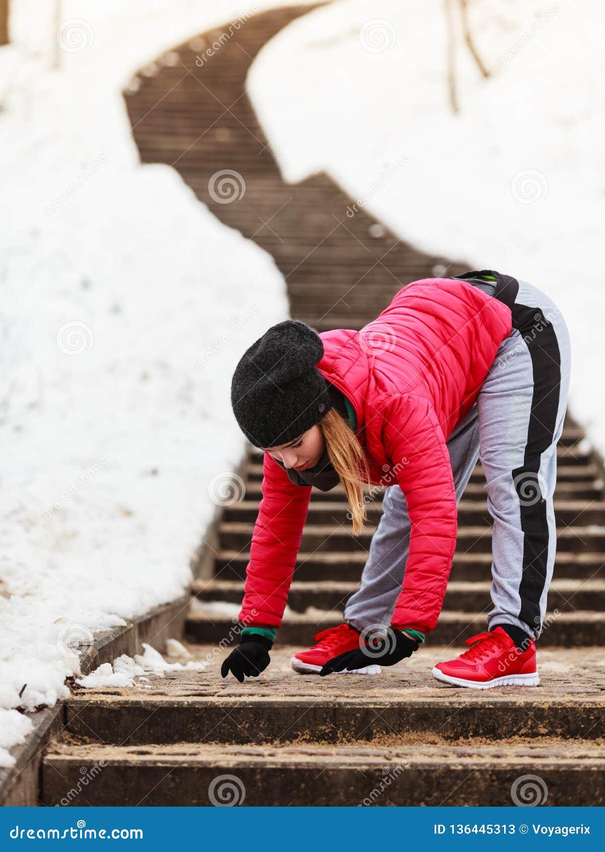 Sportswear vestindo da mulher que exercita fora durante o inverno