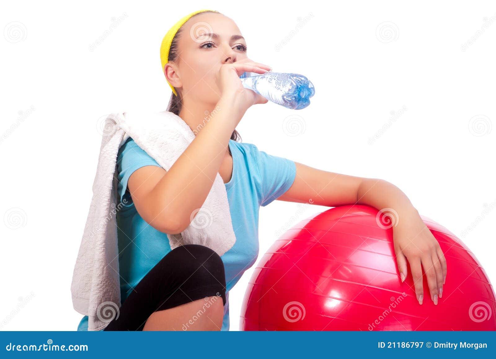 Sportswoman drinking water after training