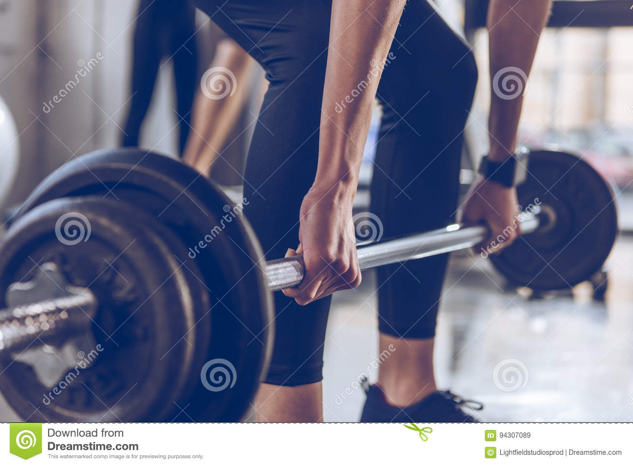 Sportswoman lifting barbell at gym workout