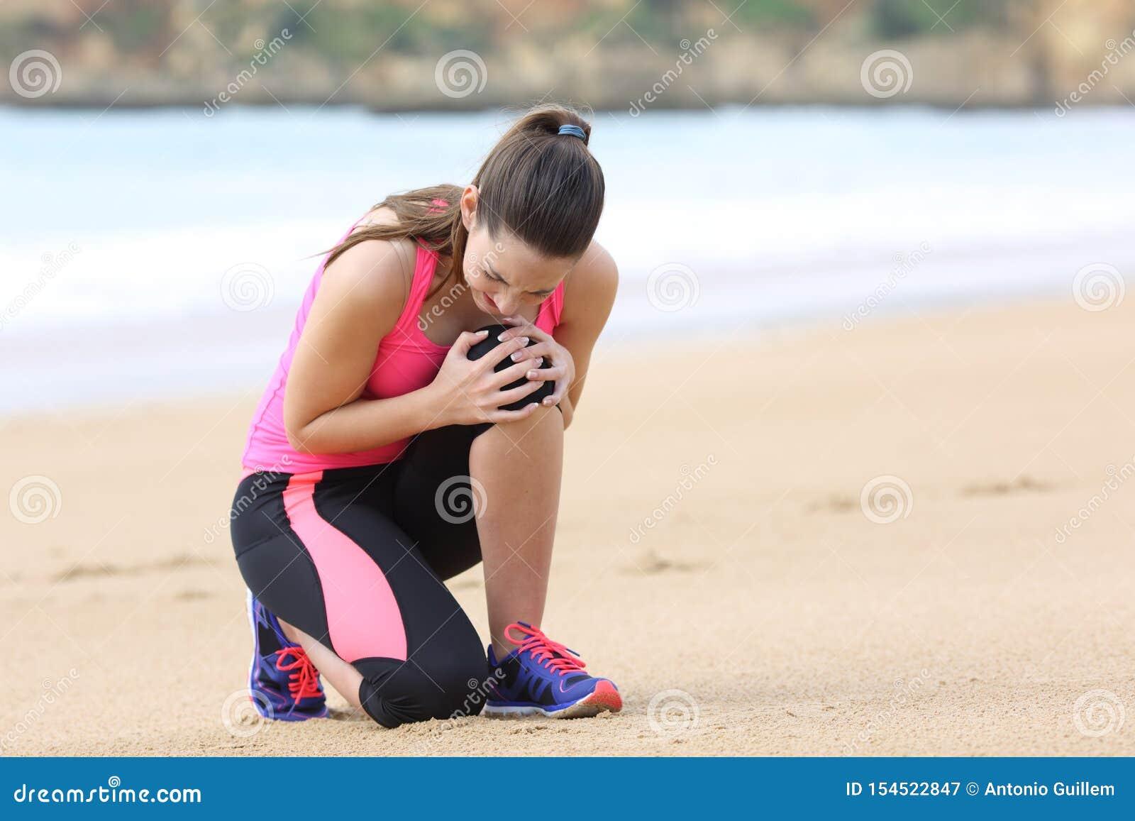 Sportvrouw die knie aan pijn na het lopen lijden