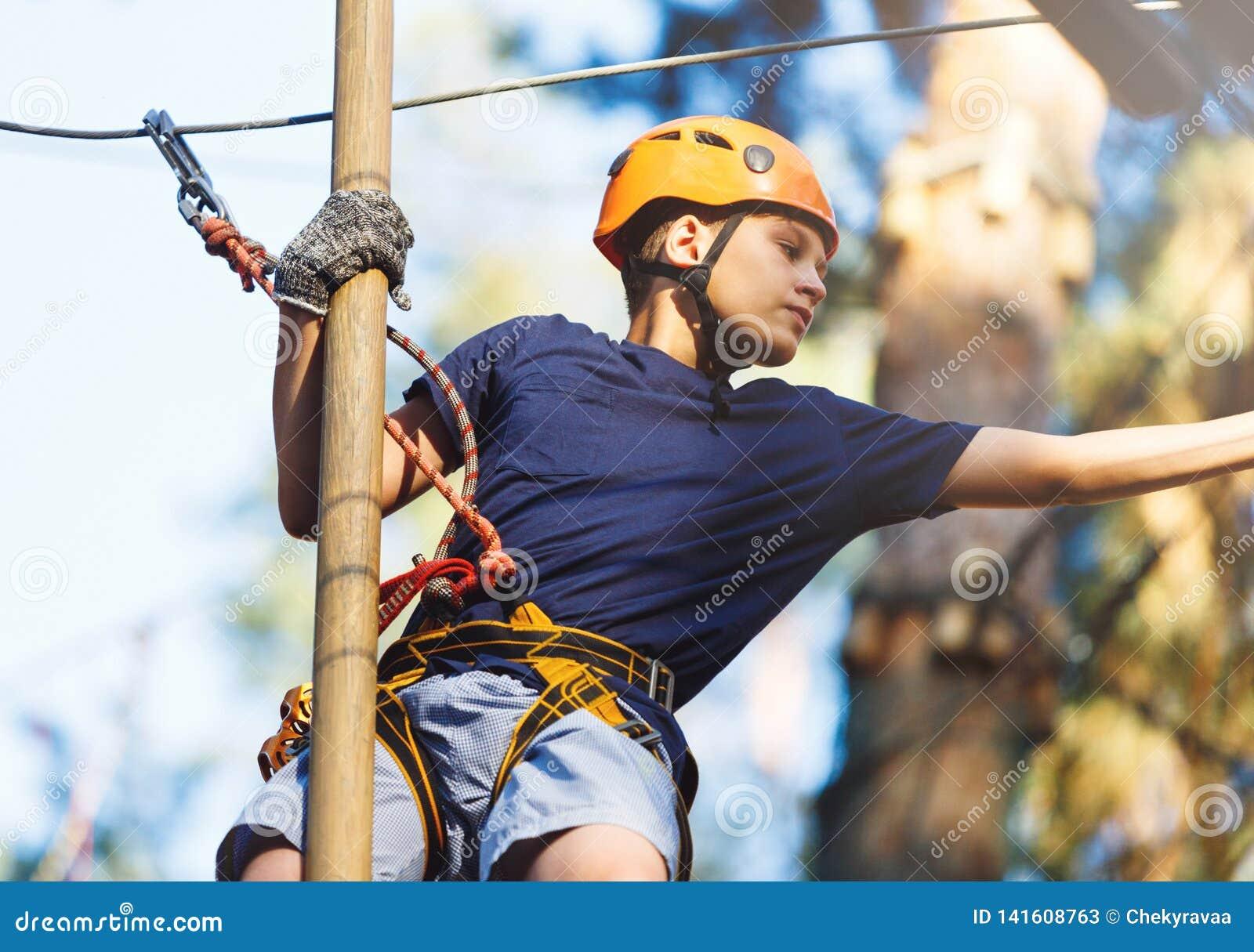 Sporty, молодой, милый мальчик в белой футболке тратит его время в парке веревочки приключения в шлеме и безопасном оборудовании