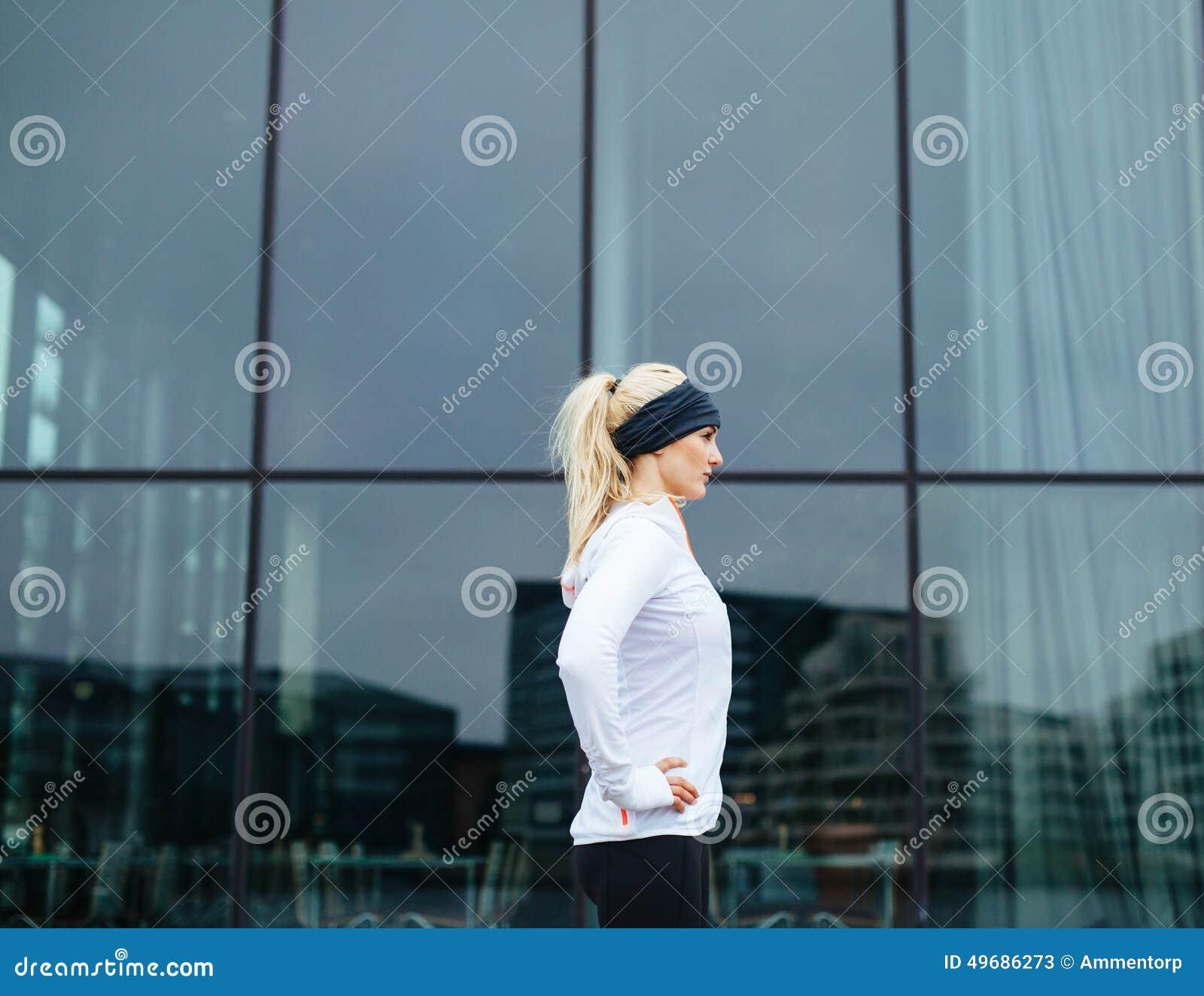 Sporty żeński przygotowywający dla jej plenerowej sesi szkoleniowa