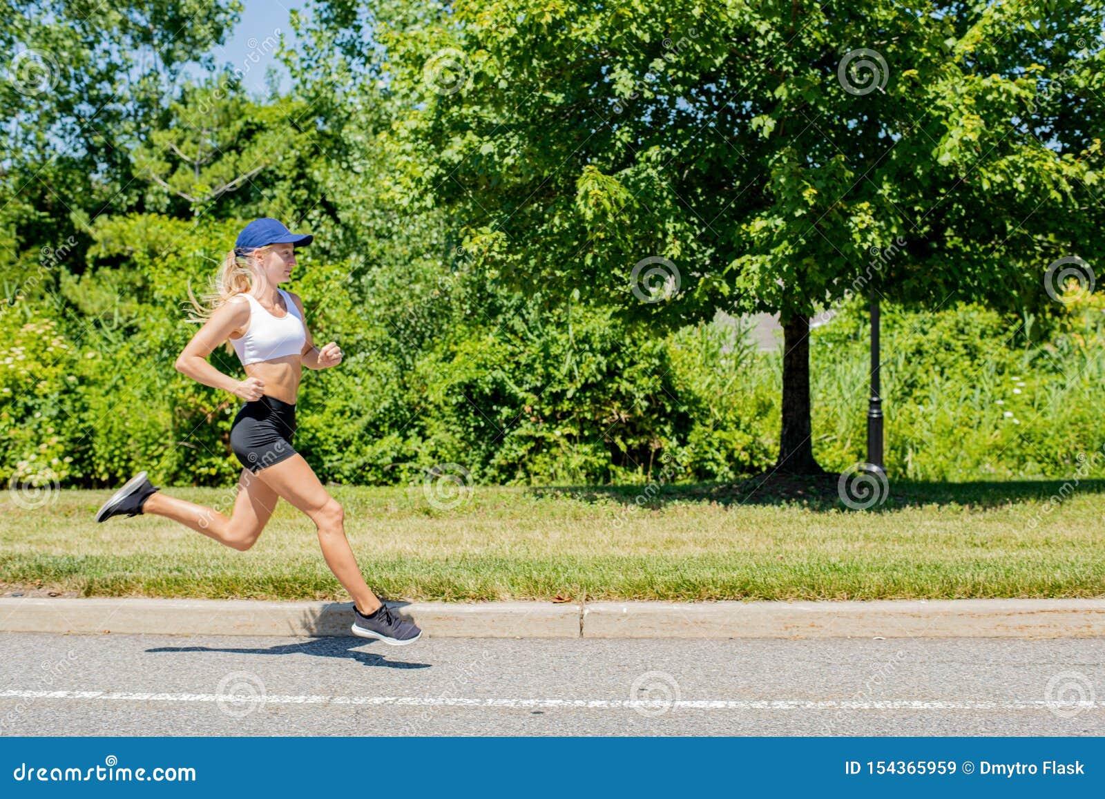 Sporty женщина в ходе следа sportswear на дороге Девушка спортсмена jogging в парке