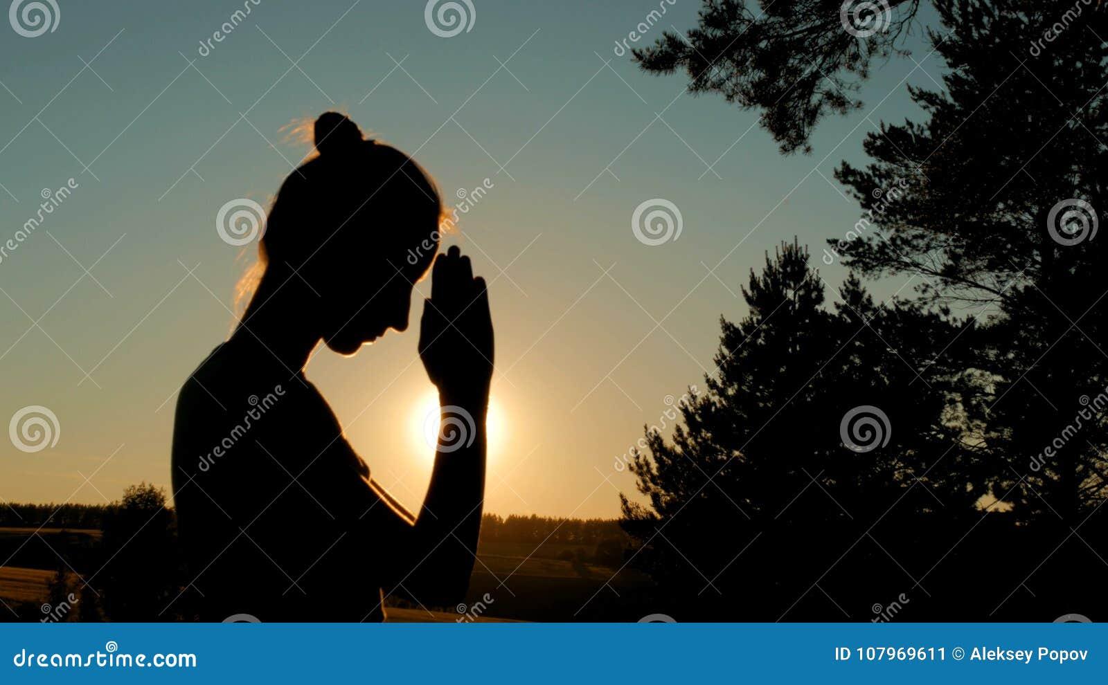 Sporty женщина моля в парке на заходе солнца