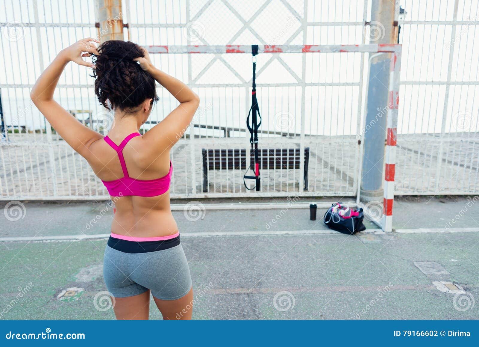Sporty женщина получая готовый для разминки trx фитнеса
