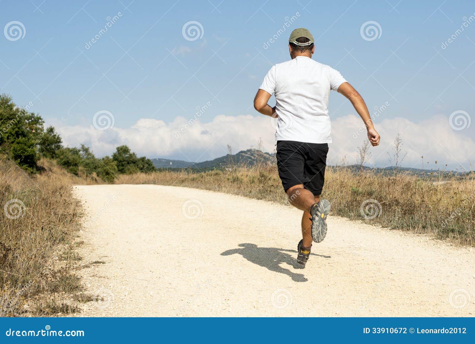Sporty человек бежать вниз с песочного следа.