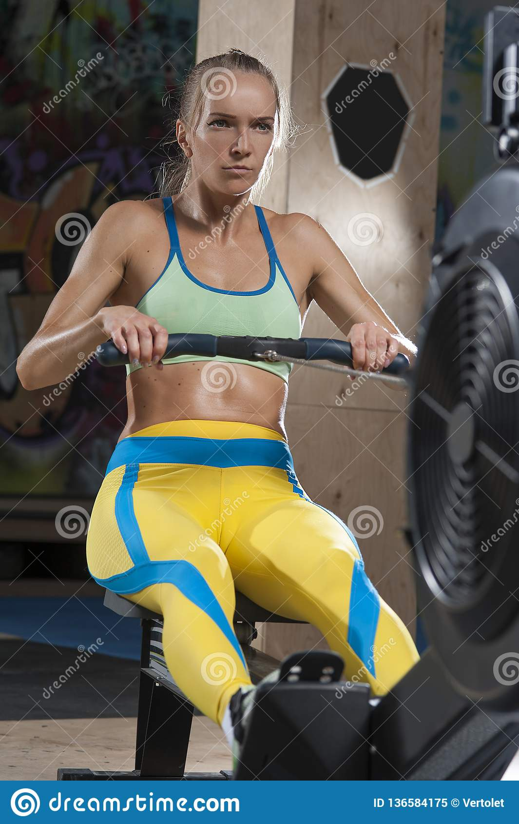 Sporty Blonde Woman Exercising On Rowing Machine Stock Image - Image