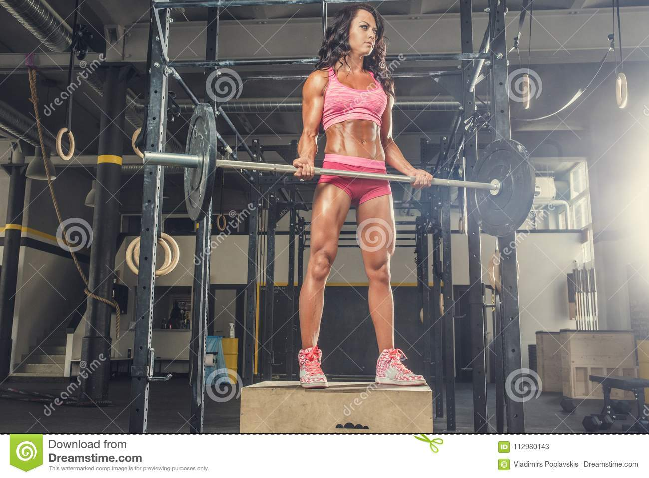 The sporty brunette female holds the barbell in a gym club.