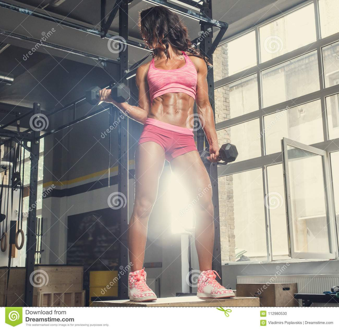 The sporty brunette female holds the dumbbellsl in a gym club.