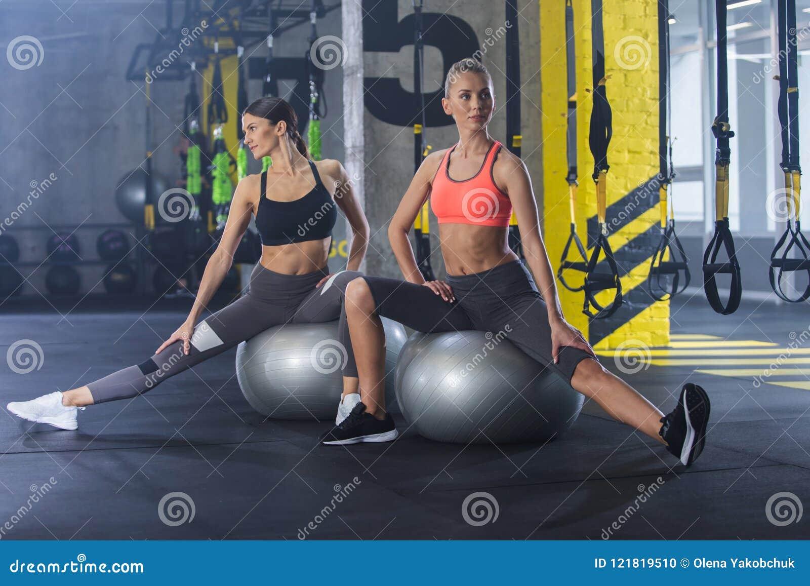 Sporty damy ćwiczą z sprawności fizycznej piłką indoors
