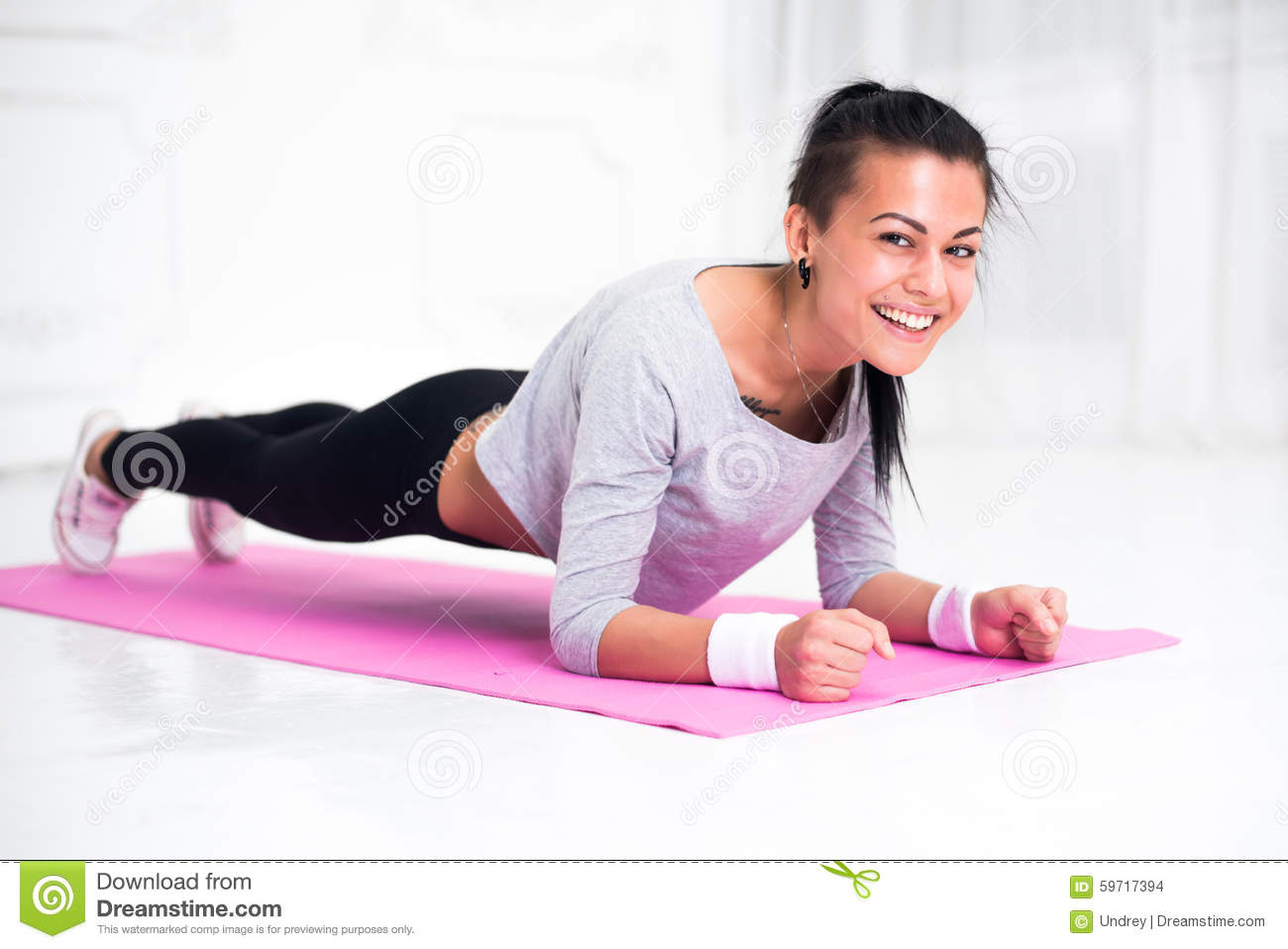 Sporty fit sliming girl doing plank exercise in