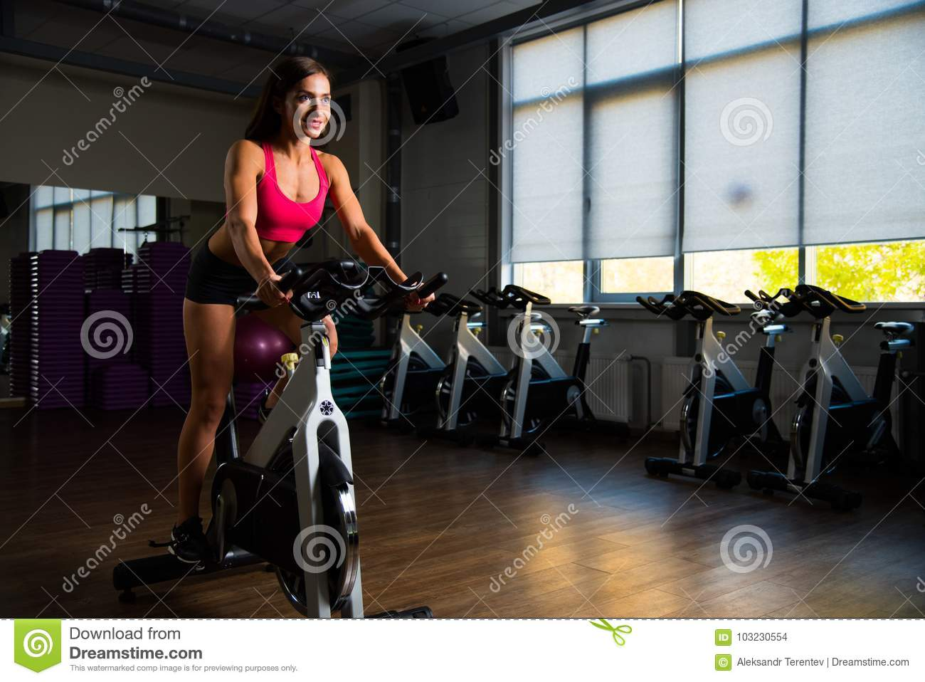 Sporty girl in fitness hall on cycle.