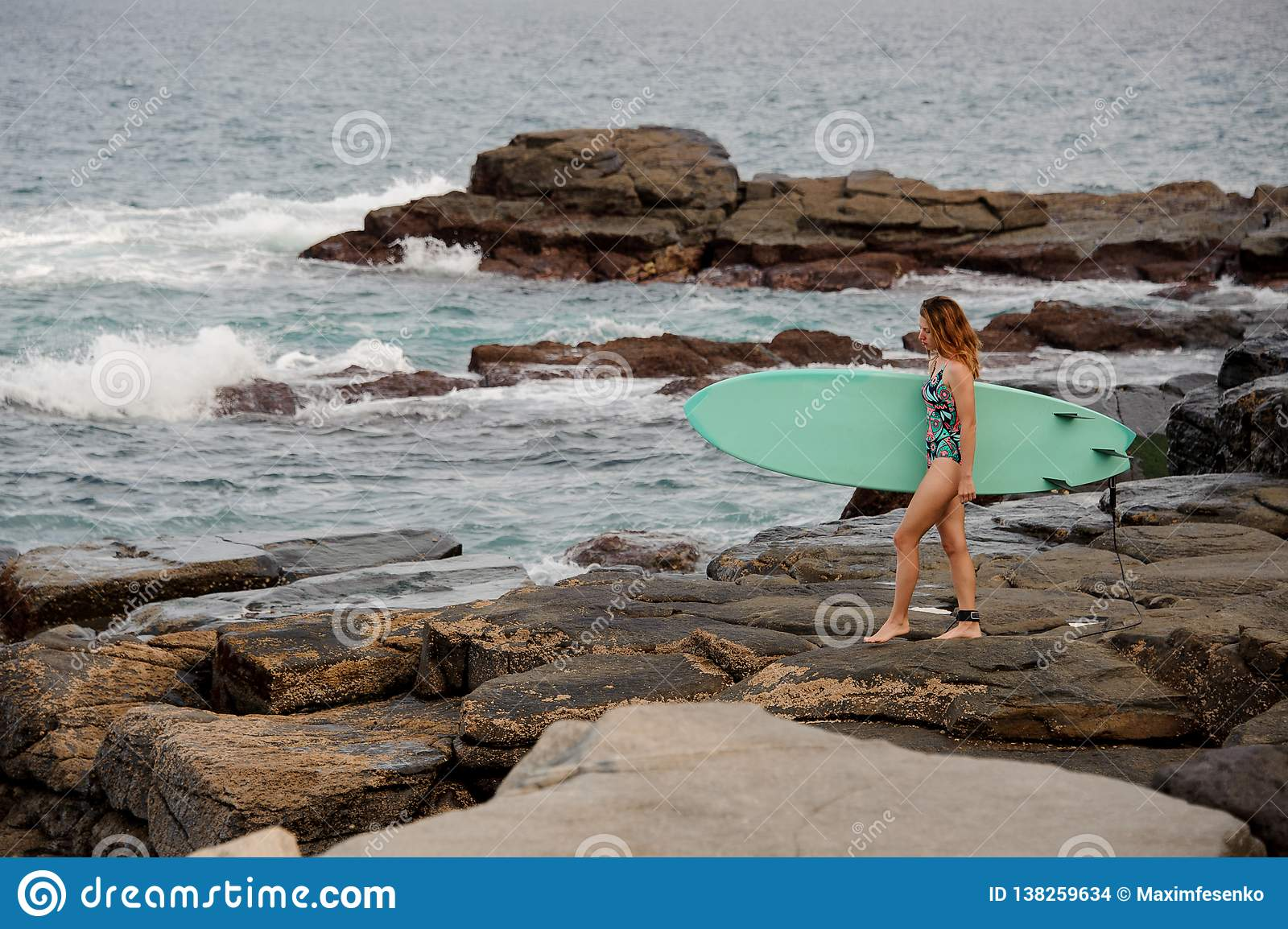 Sporty girl in the multi colored swimsuit walking with the surf on the rocks on the beach