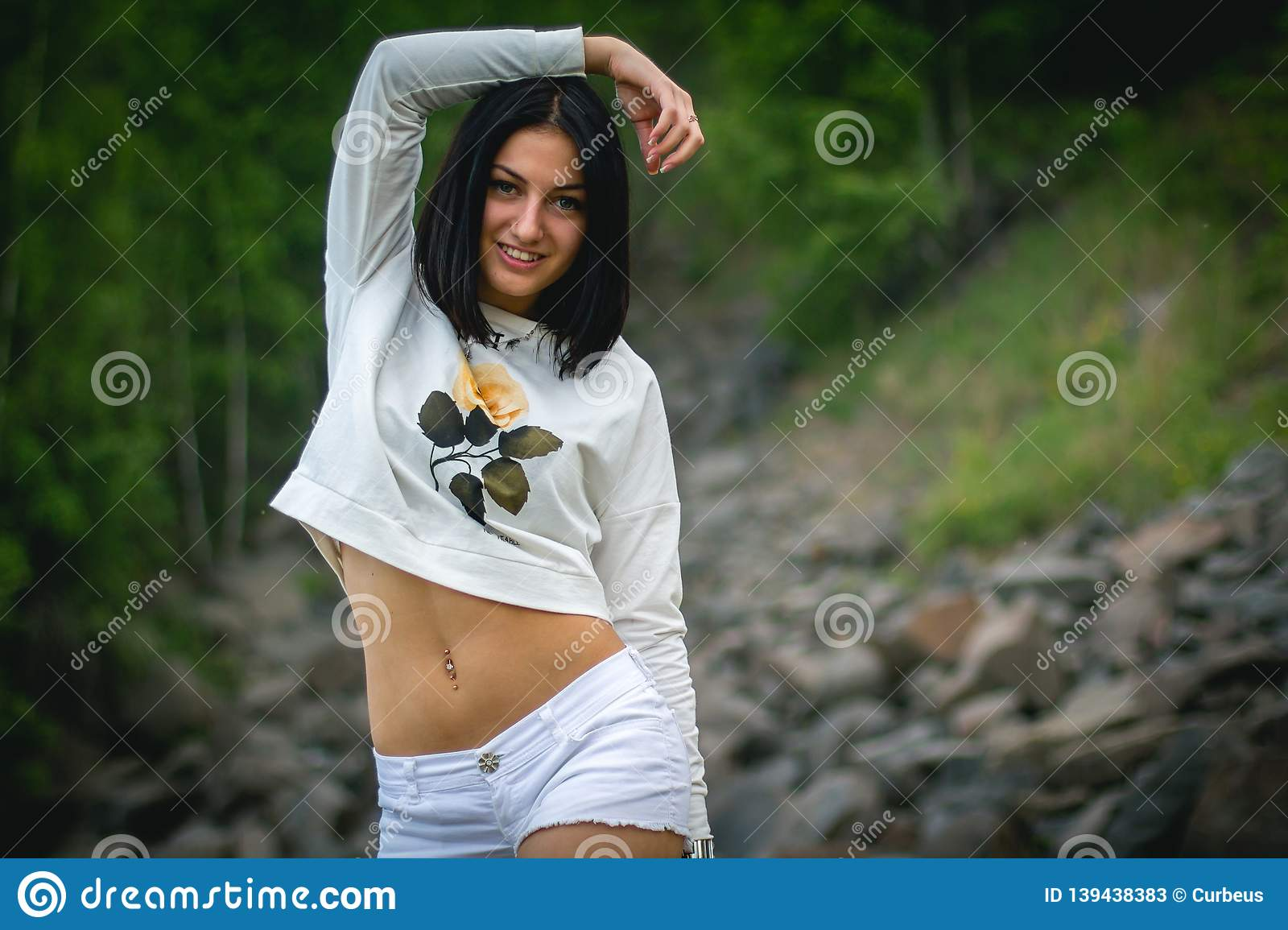 A sporty girl with an open tummy stopped to smile, her hand raised behind her head. Green forest or Park in the background. Female