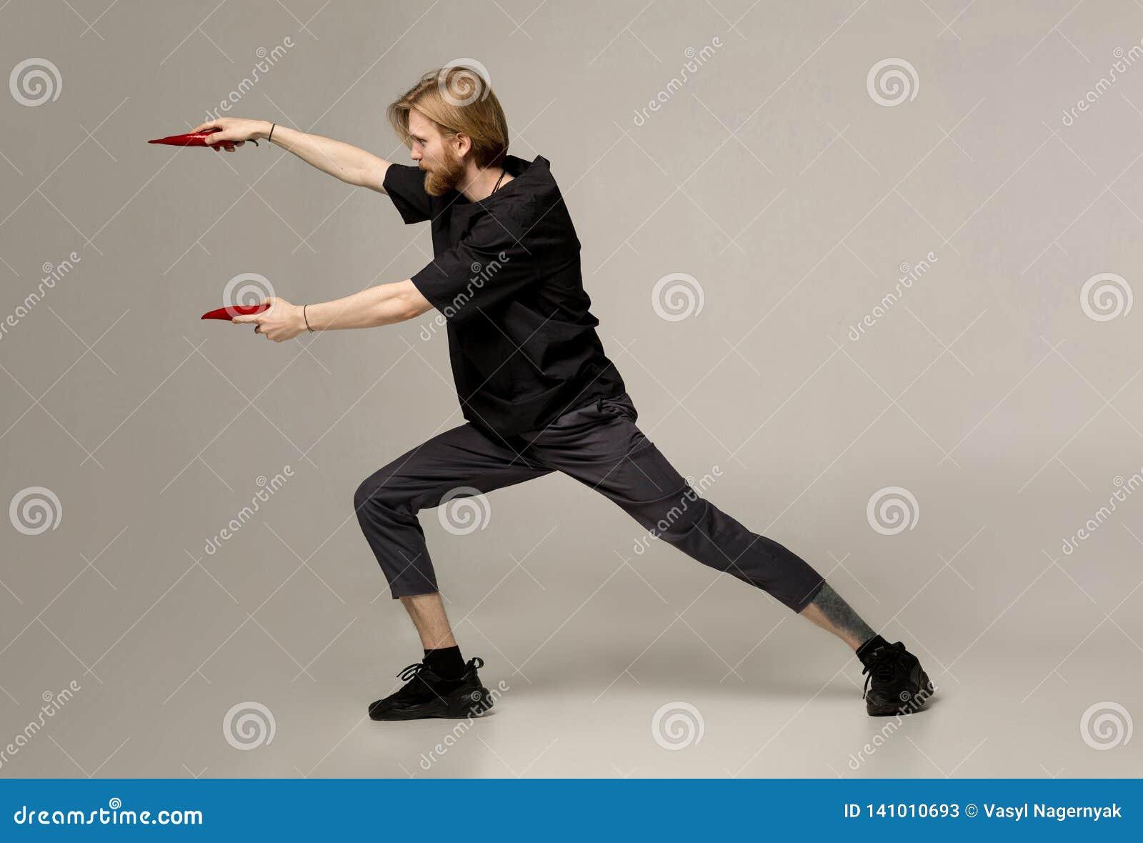 Sporty i bojowy pojęcie Facet pozuje w karate pozie z dwa czerwonymi pieprzami w rękach