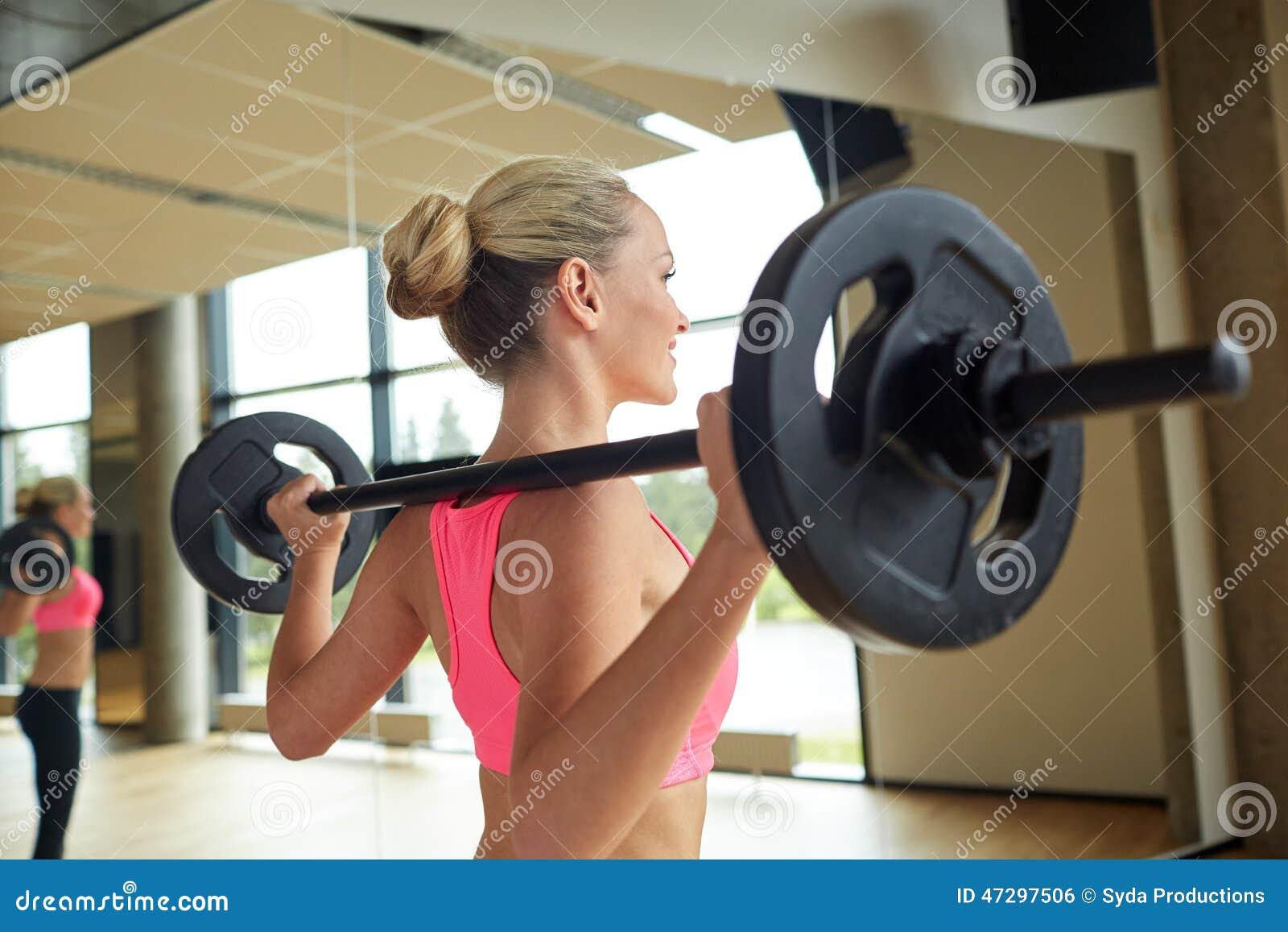 Sporty kobieta ćwiczy z barbell w gym