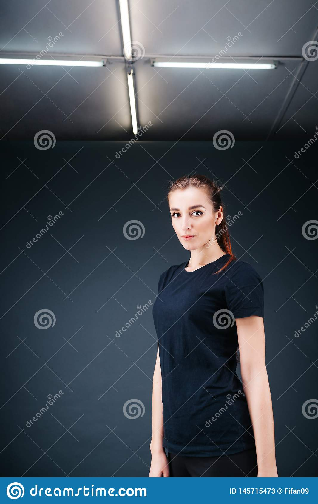 Sporty-looking girl in a black T-shirt and leggings