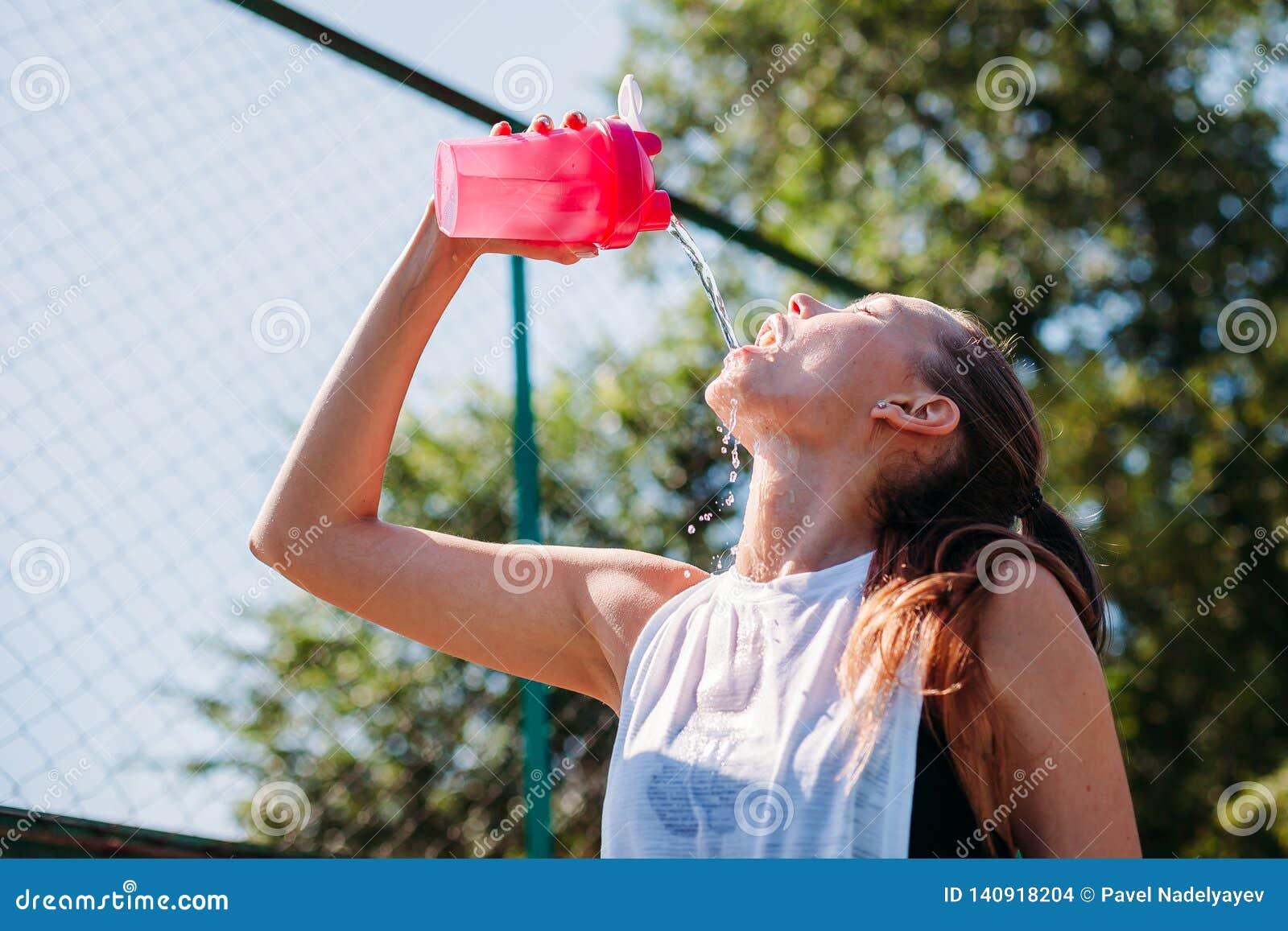 Sporty młoda blondynki kobieta z sporty butelką z chłodno wodą nalewa wodę na ona na sporta polu