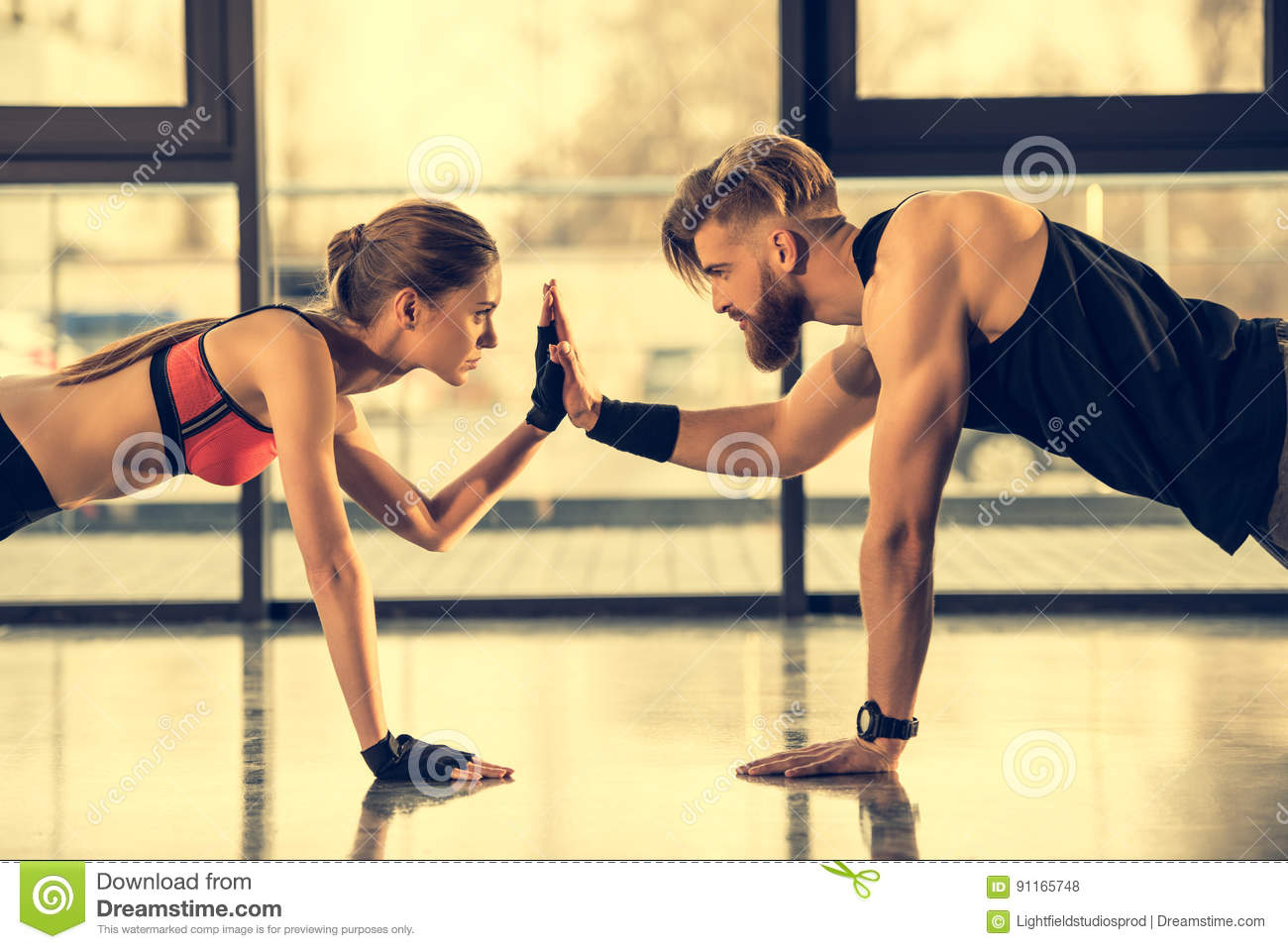 Sporty man and woman doing plank exercise and giving high five