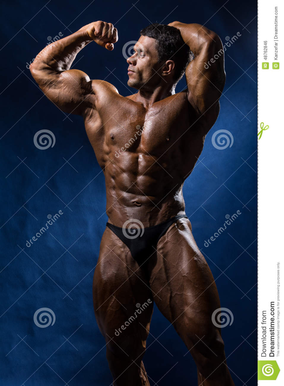 c984f77bcdd Sporty muscular man bodybuilder shows his body and strength on a blue  background.