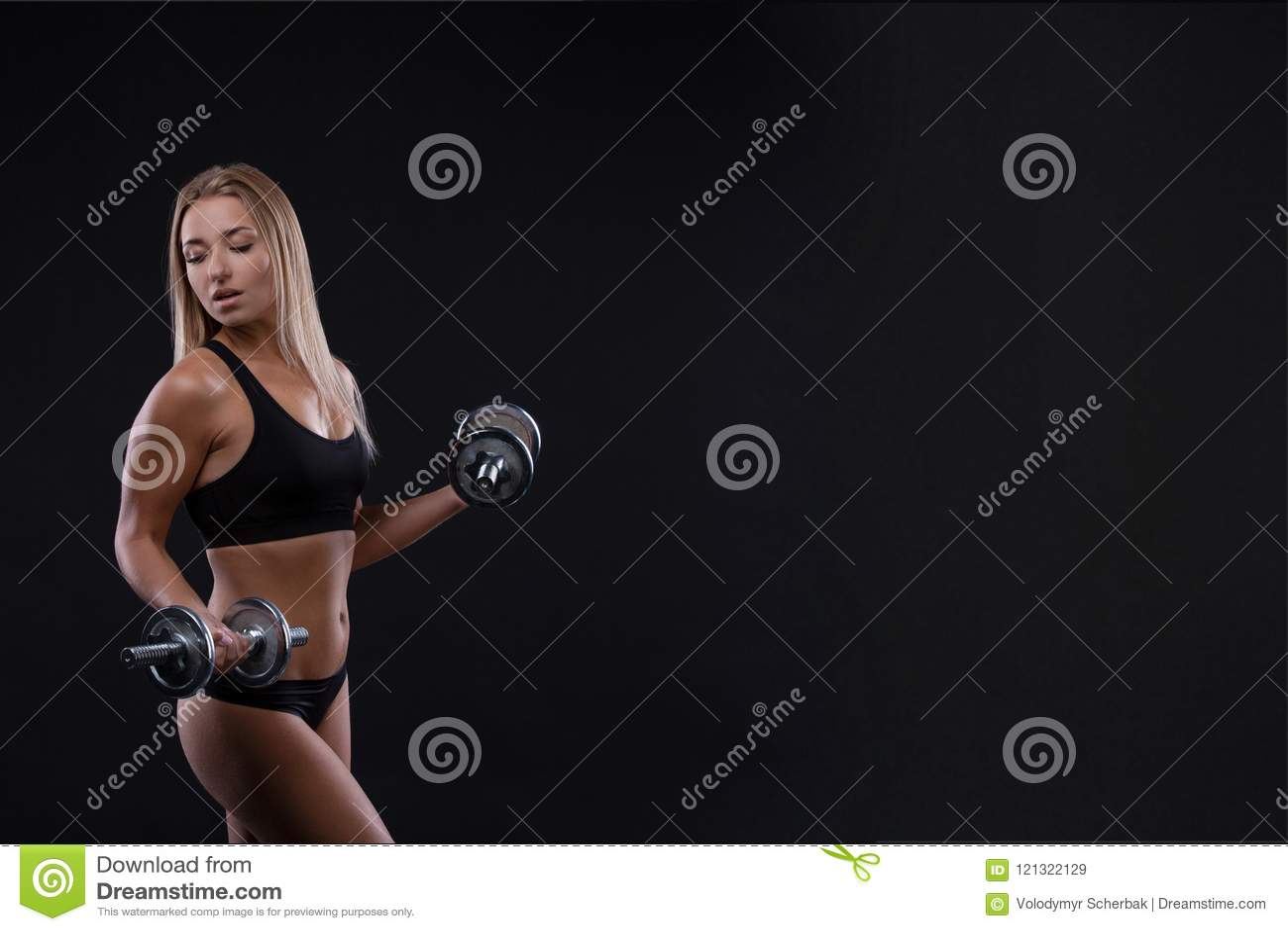 Sporty piękna kobieta ćwiczy przy czarnym tłem zostawać dysponowaną z dumbbells robi sprawności fizycznej