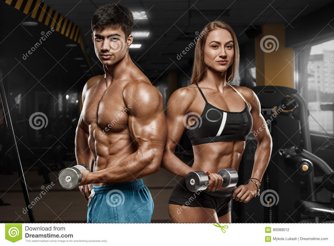 Sporty couple showing muscle and workout in gym. Muscular man and wowan