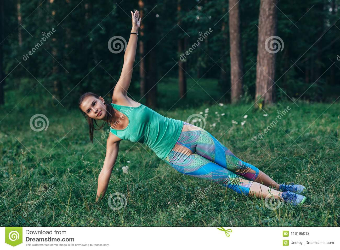 Sporty slim sportswoman doing side plank yoga pose standing on grass in summer morning