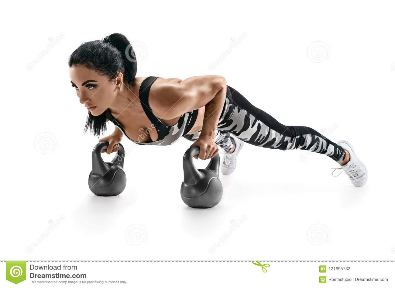 Sporty woman doing push ups exercise with kettlebells.