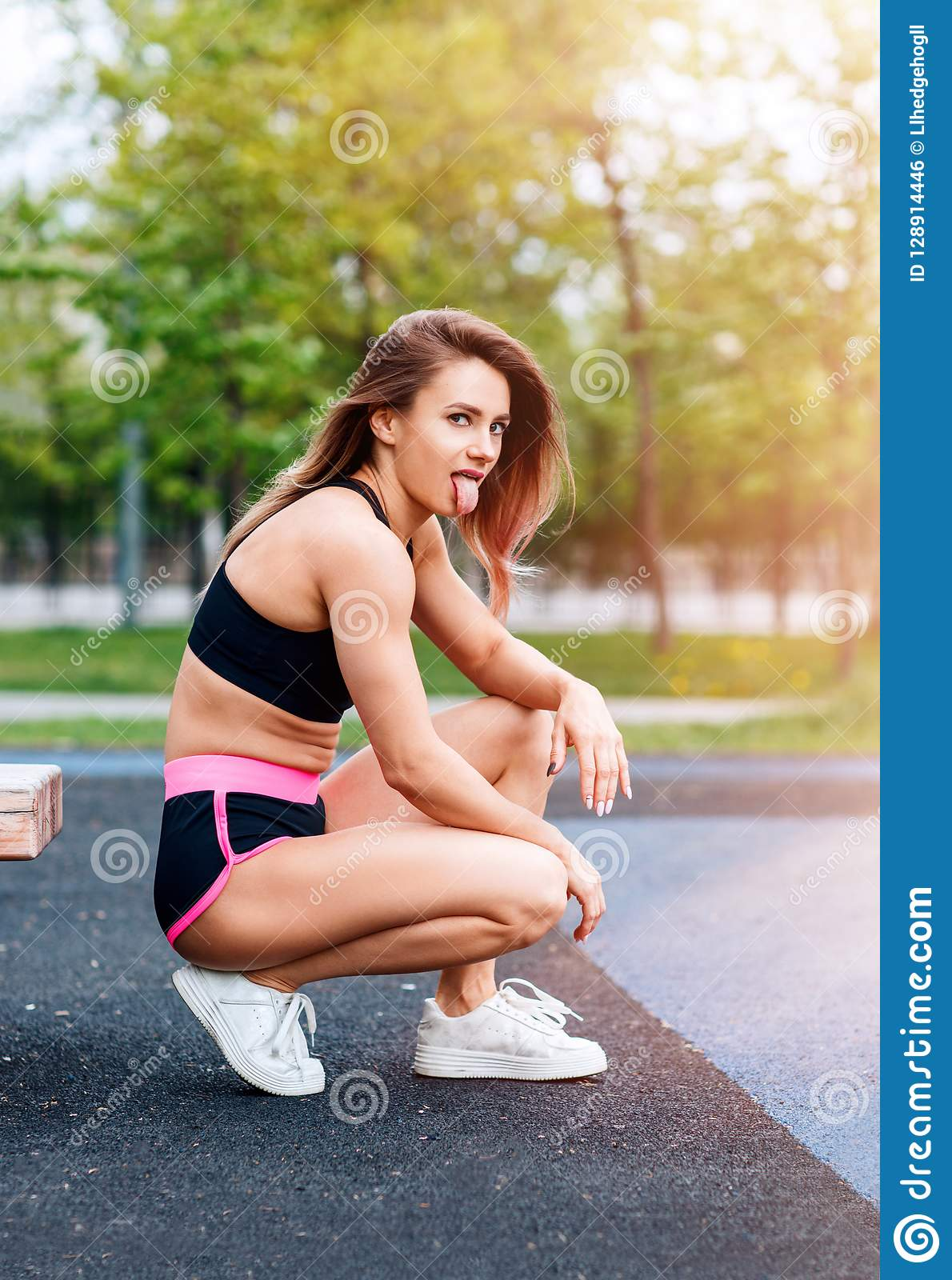 Sporty woman with perfect athletic body shows tongue