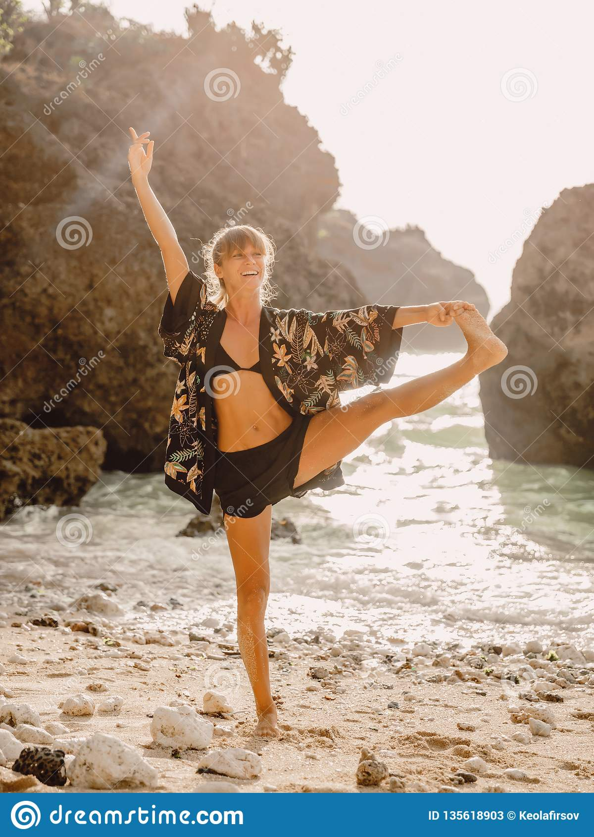 Sporty woman practice gymnastics at beach with sunset or sunrise