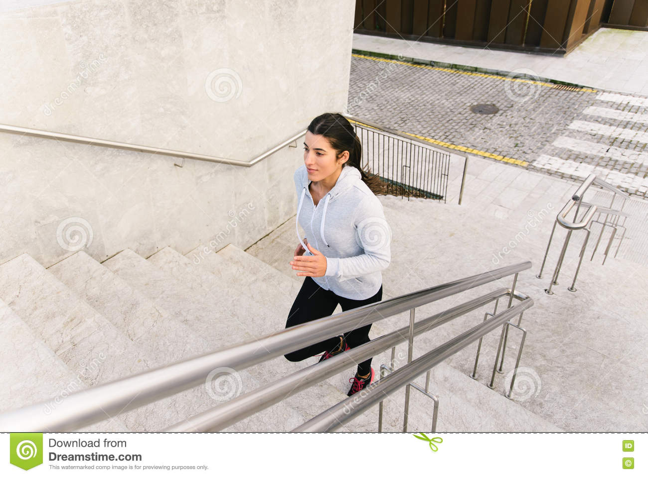 Sporty woman running and climbing stairs