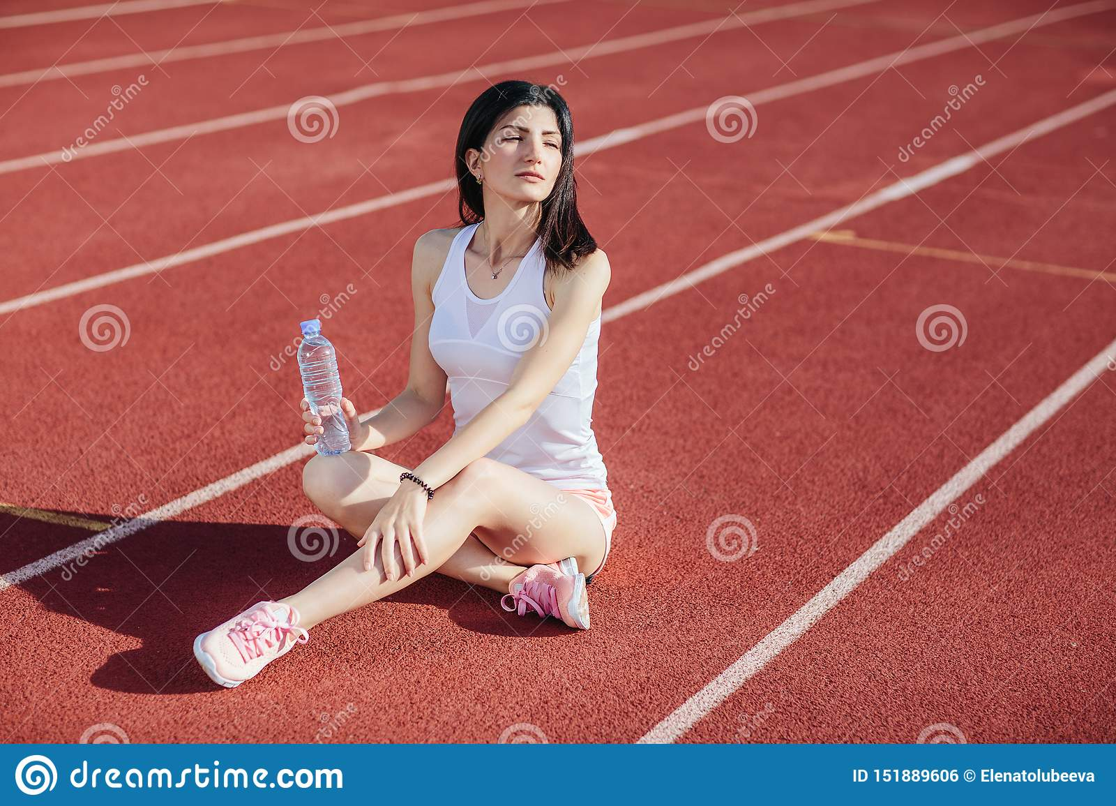 Sporty woman sitting on treadmill with bottle of water
