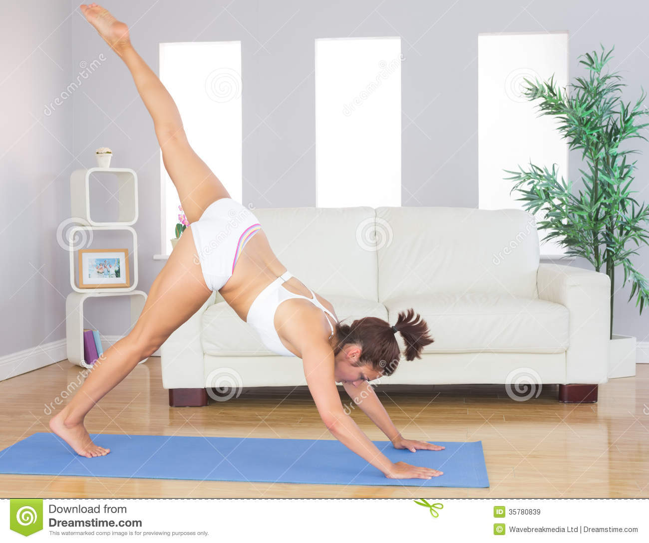 Sporty woman stretching her body with yoga pose on an for Living room yoga timetable