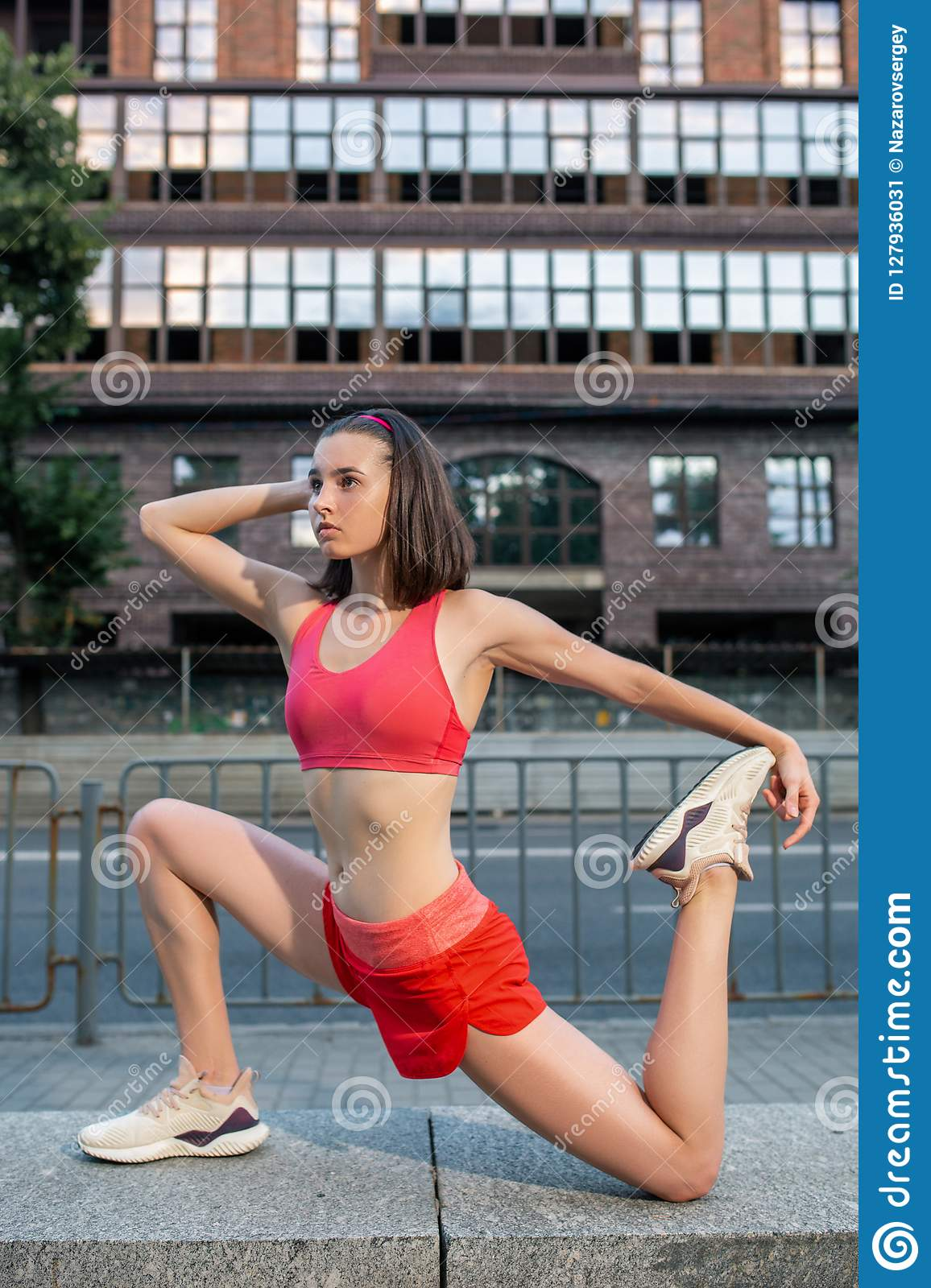 Sporty woman stretching and warming up legs before running urban fitness workout. Sport and healthy lifestyle concept.