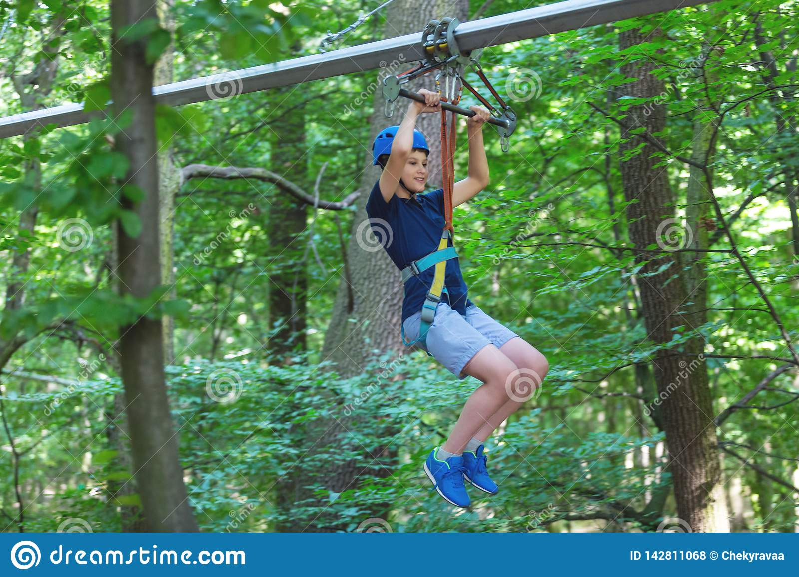 Sporty, young, cute boy in white t shirt spends his time in adventure rope park in helmet and safe equipment in the park
