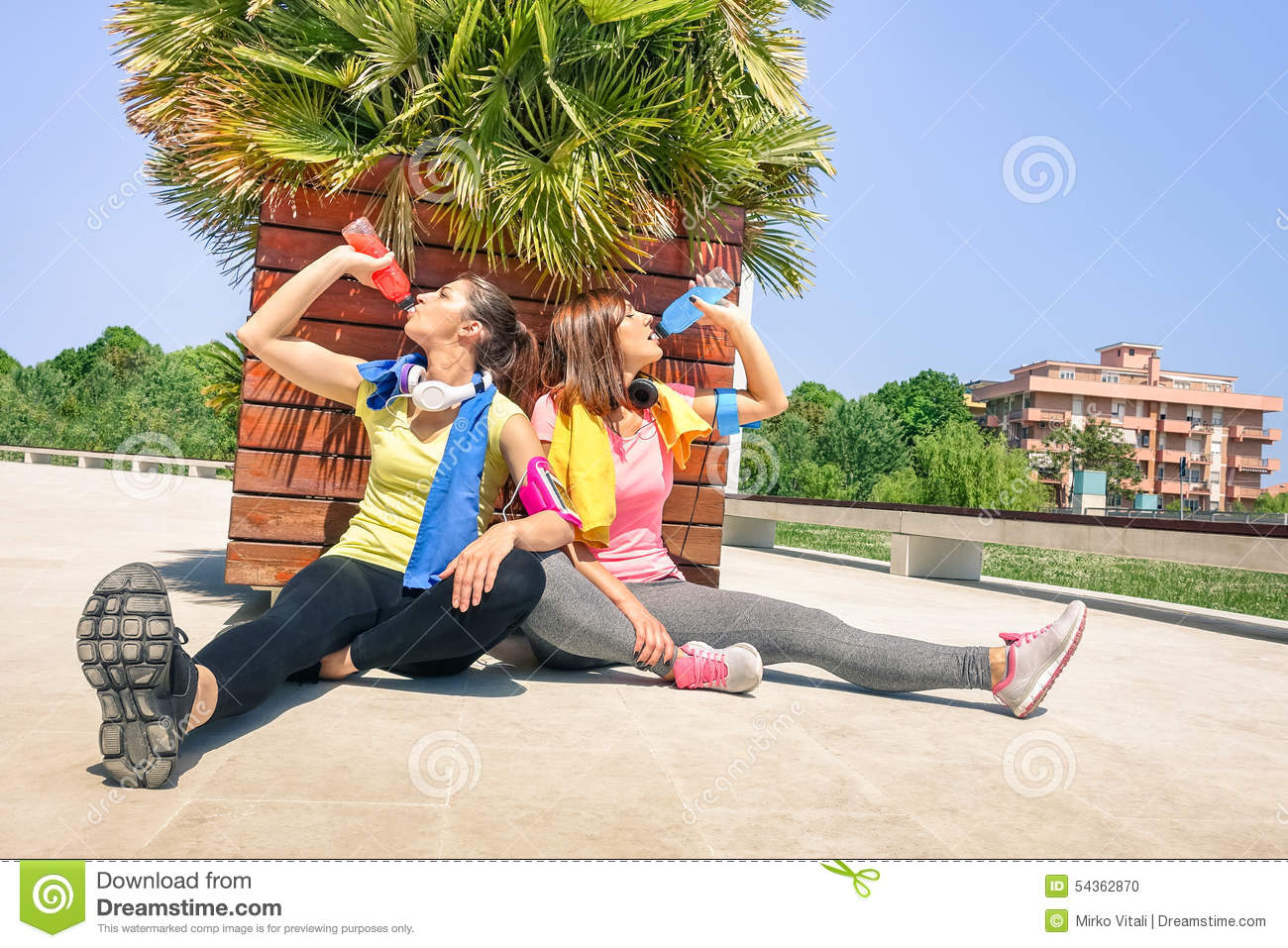 Sporty young women drinking energetic juice at run training