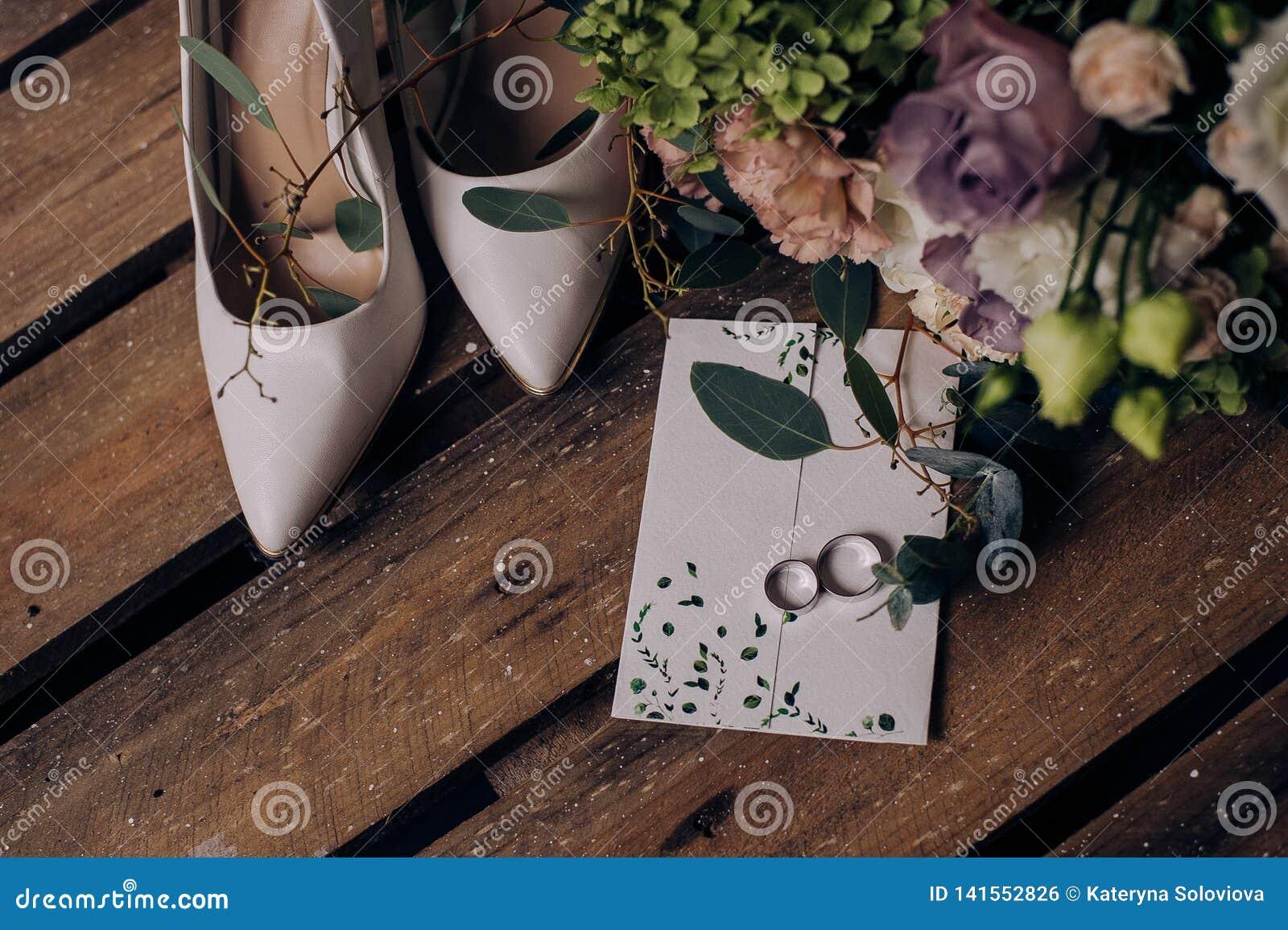 Sposa accessoria di nozze Scarpe beige alla moda, orecchini, anelli di oro, fiori, giarrettiera su fondo di legno