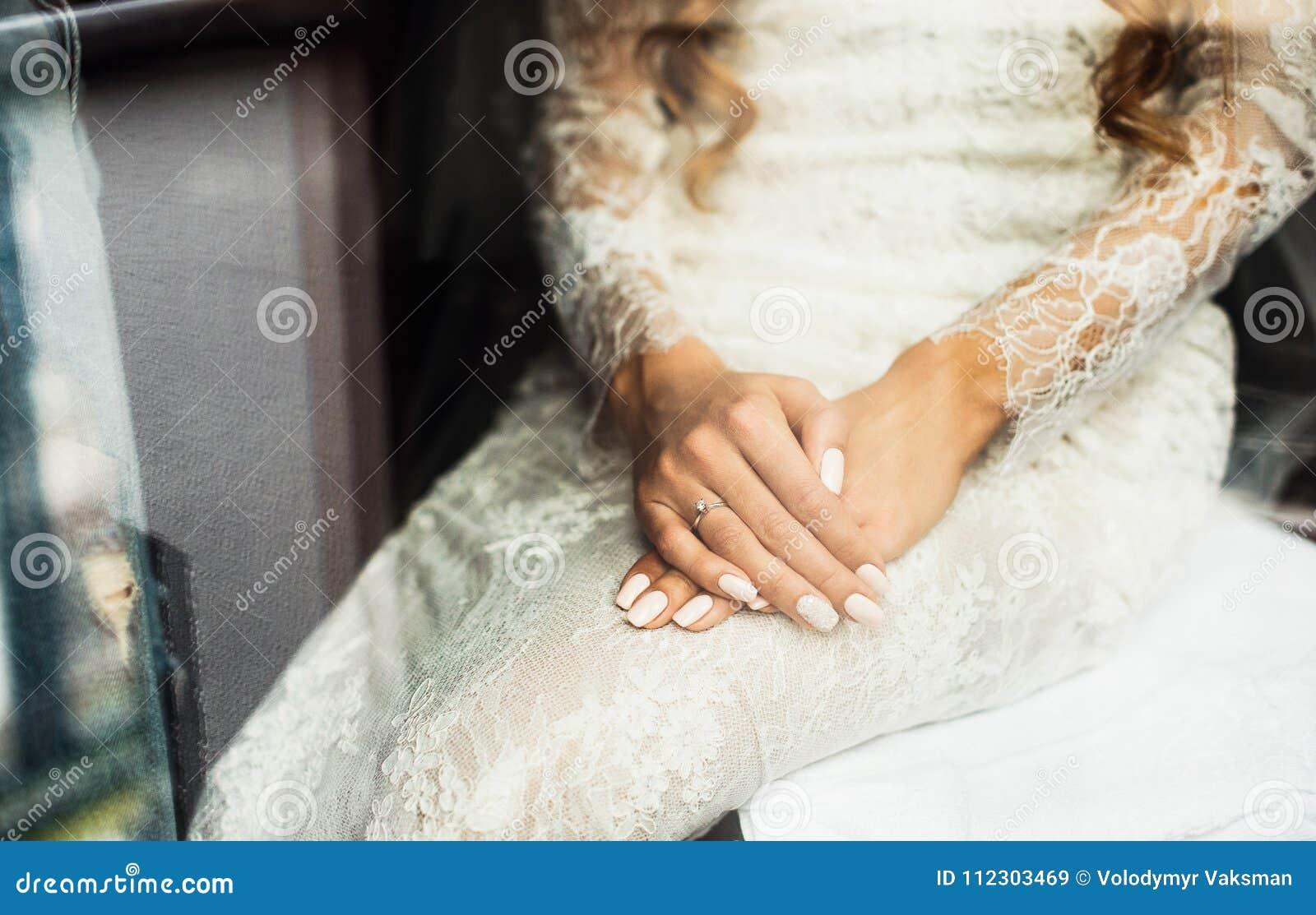 Sposa bionda elegante che mette sul primo piano degli orecchini, preparante per