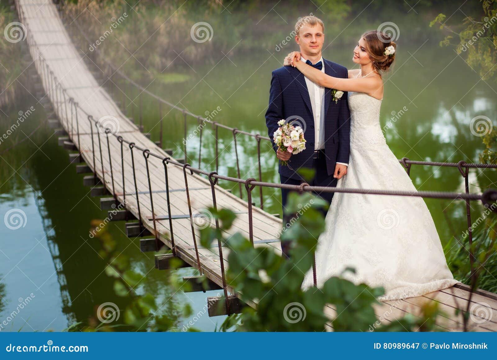Sposa che abbraccia sposo sul ponte fotografia stock for Sposa che corre