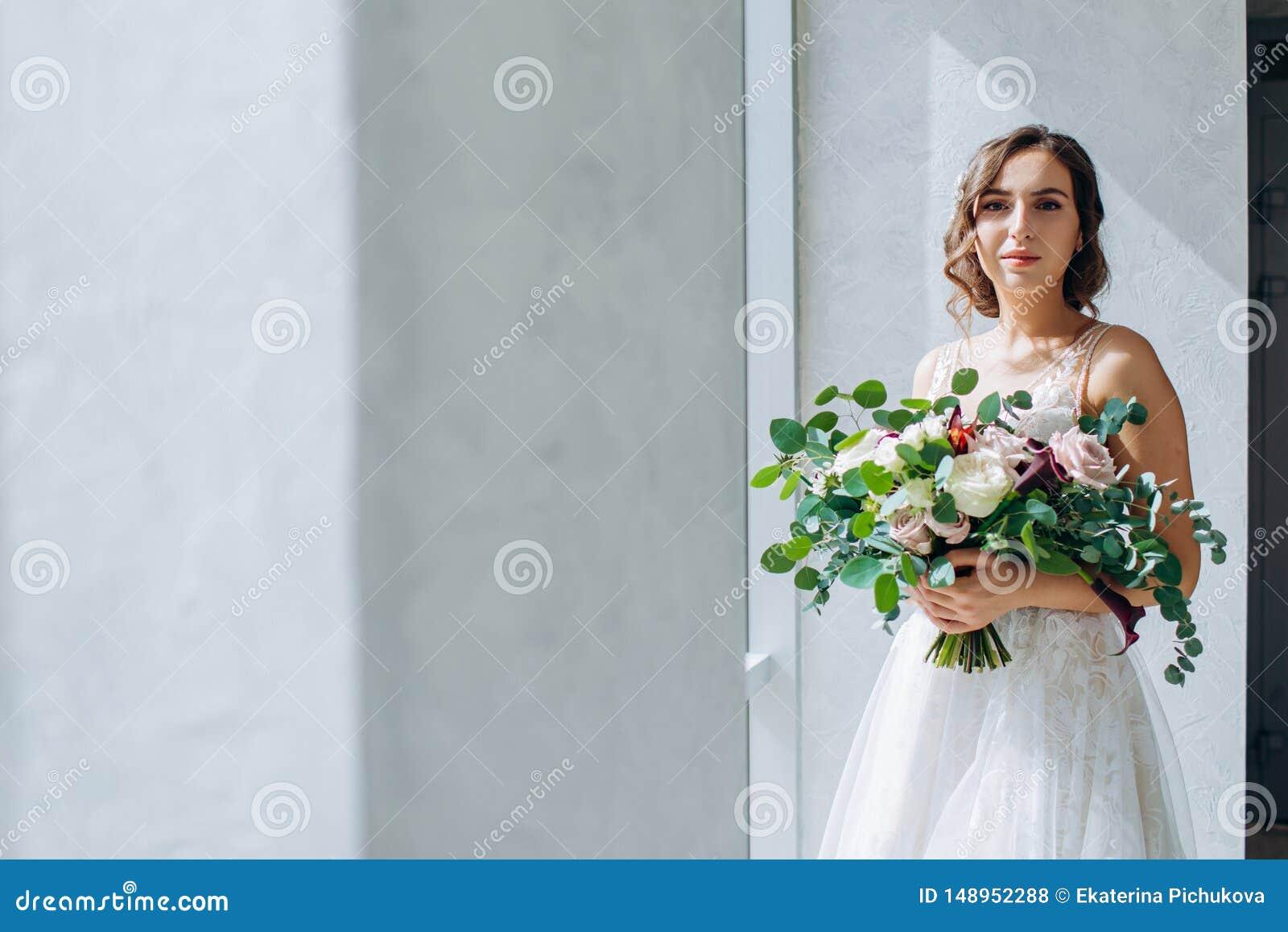 Sposa con un mazzo di nozze delle rose bianche in mani