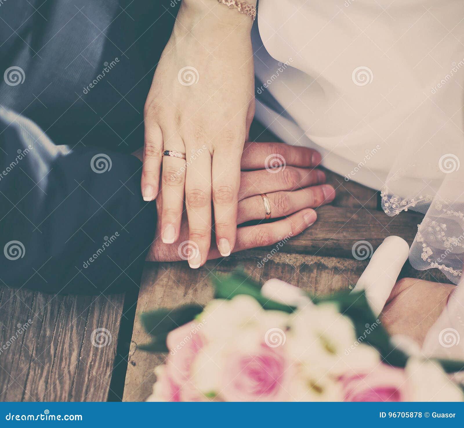 Sposa delle coppie di nozze e sposo che si tengono per mano con gli anelli, mazzo dei fiori
