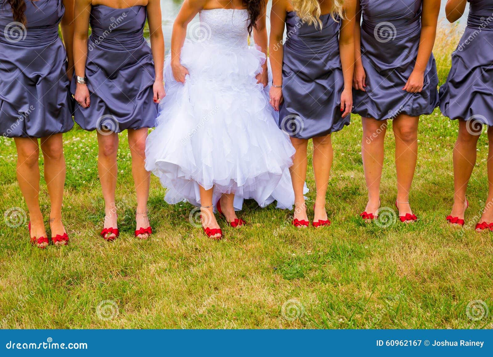 8a75f87d7cd6 La sposa e le damigelle d onore che giudicano loro si agghinda un pezzo per  ostentare le loro scarpe rosse mentre stanno sull erba verde
