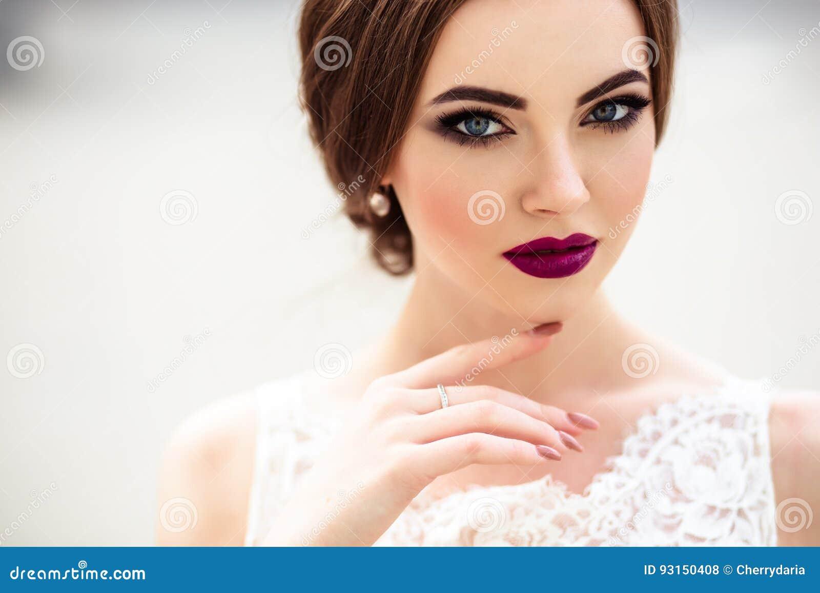 Sposa splendida con trucco di modo e acconciatura in un vestito da sposa di lusso