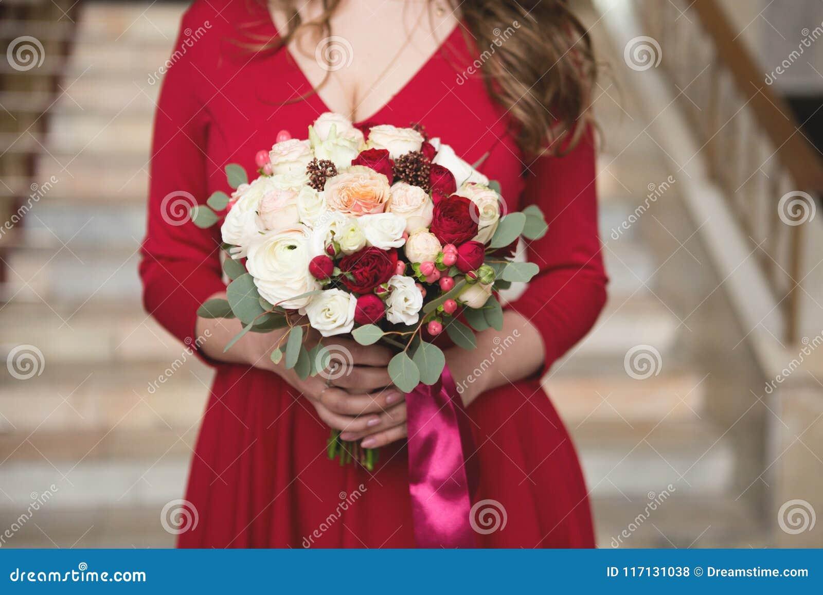 Sposa in un vestito rosso Damigella d onore in un vestito rosso Mazzo di nozze con un nastro rosso