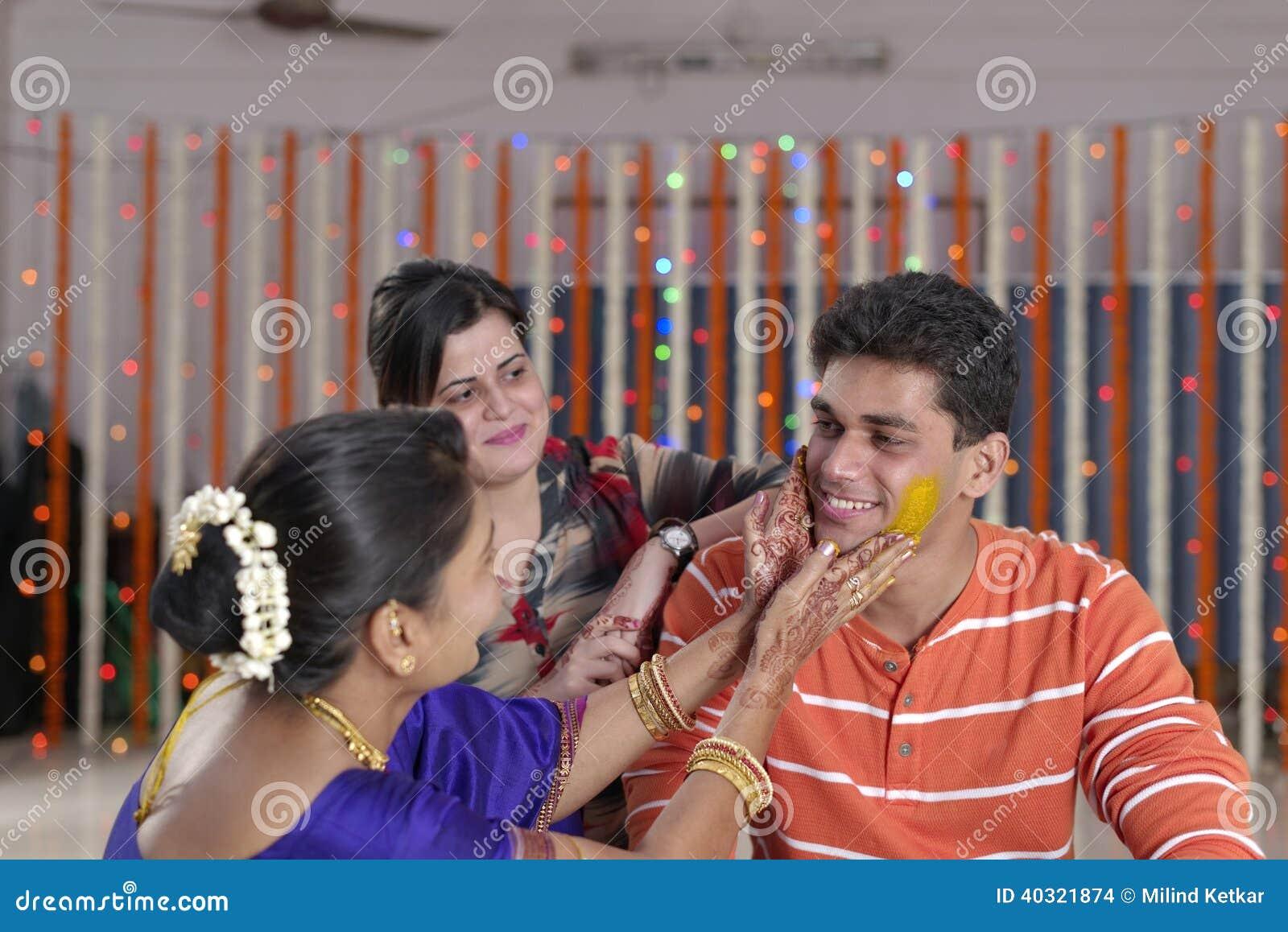 Sposo indù indiano con la pasta della curcuma sul fronte con la madre