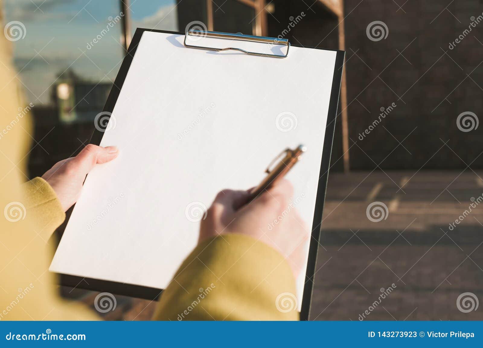 Spot omhoog van de tablet voor het document in de handen van het meisje tegen de achtergrond van het glascentrum