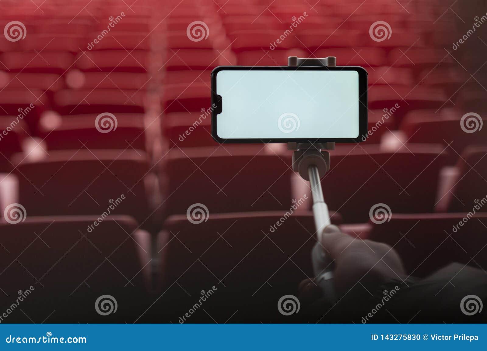 Spot op Smartphone met een selfiestok in de handen van een mens op de achtergrond van de tribunes De kerel neemt een selfie bij